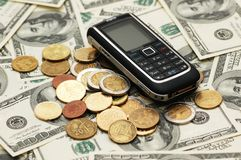 Mobile phone with coins Stock Photo