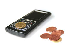 Mobile phone and coins Royalty Free Stock Image