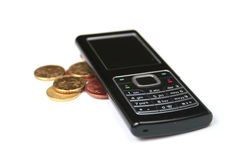 Mobile phone and coins Royalty Free Stock Photos