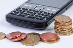 Mobile phone with coins closeup. Royalty Free Stock Image