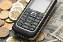 Mobile phone with coins and do Royalty Free Stock Image