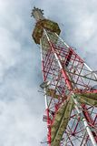 Mobile phone communications antenna tower telecommunications tower perspective. Mobile phone communication antenna tower with cloud on center blue sky Royalty Free Stock Images