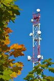 Mobile phone communication radio tv tower, mast, cell microwave antennas and transmitter against the blue sky and trees Royalty Free Stock Photo
