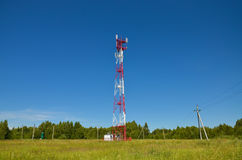 Mobile phone communication radio tv tower, mast, cell microwave antennas and transmitter against the blue sky and trees. Mobile phone communication radio tv stock photography