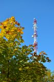 Mobile phone communication radio tv tower, mast, cell microwave antennas and transmitter against the blue sky and trees. Mobile phone communication radio tv royalty free stock image