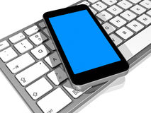 Mobile phone on a computer keyboard Royalty Free Stock Photo