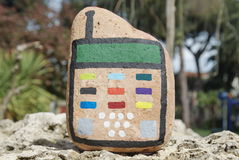 Mobile phone concept painted on a stone. Child water paint over a stone as first handy idea Royalty Free Stock Photos