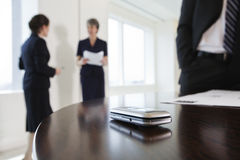 Mobile phone on conference table during meeting. Stock Photo