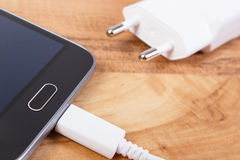 Mobile phone with connected plug of charger, smartphone charging Royalty Free Stock Photography