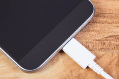 Mobile phone with connected plug of charger, smartphone charging Stock Images