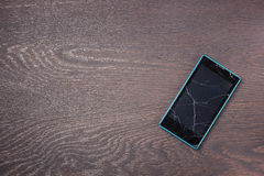 The mobile phone with cracks on the screen. The mobile phone with cracks on the screen on a dark wooden flooring, the top view royalty free stock image