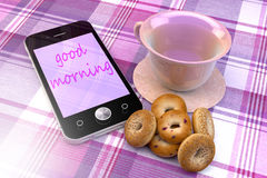 Mobile phone with cup and cupcakes Royalty Free Stock Photos