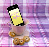 Mobile phone with cup and cupcakes Royalty Free Stock Photography