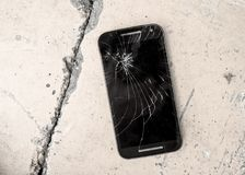 Mobile phone device scratched and broken crack touch screen abandoned on street concrete ground in repair and fix smart phone serv. Ice concept stock photo