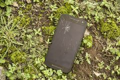 Mobile phone device scratched and broken crack touch screen abandoned on street grass ground in repair and fix smart phone service. Concept royalty free stock photography