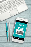 Mobile phone with discount coupon computer and coffee Royalty Free Stock Photo