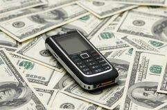 Mobile phone and dollars. Mobile phone and dollar bank notes Royalty Free Stock Photo