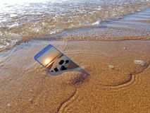 Mobile phone dropped into the water from the ocean stock photography