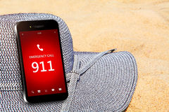 Mobile phone with emergency number 911 on the beach Royalty Free Stock Photo