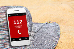 Mobile phone with emergency number 112 on the beach Stock Photography