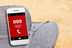 Mobile phone with emergency number 000 on the beach. Focus on screen Royalty Free Stock Image
