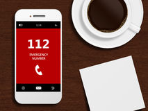 Mobile phone with emergency number 112 lying on desk. Mobile phone with emergency number 112 lying on wooden desk Stock Photo