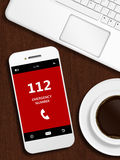 Mobile phone with emergency number 112 lying on desk. Mobile phone with emergency number 112 lying on wooden desk Royalty Free Stock Photo