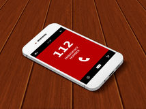 Mobile phone with emergency number 112  lying on table. Mobile phone with emergency number 112  lying on wooden table Royalty Free Stock Photo