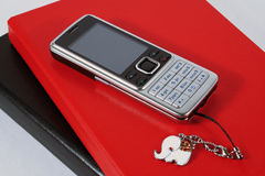 Mobile phone with fancy accessory. On agendas Royalty Free Stock Photo