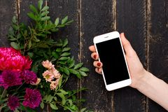 Mobile phone in female hand and a bouquet of flowers on a black wooden background royalty free stock photos
