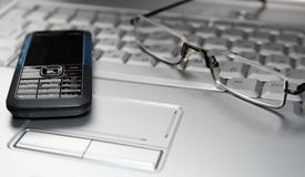 Mobile phone and glasses on laptop Royalty Free Stock Image