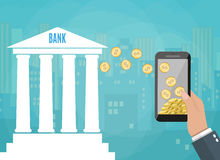 Mobile phone with gold coins and bank building Stock Photo