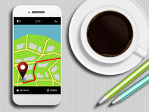 Mobile phone with gps application, coffee and pencils lying on t. Mobile phone with gps application, coffee and pencils lying on white tablecloth Royalty Free Stock Images