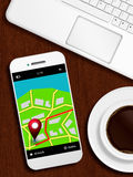 Mobile phone with gps application, laptop and coffee lying od de. Mobile phone with gps application, laptop and coffee lying od wooden desk Royalty Free Stock Images