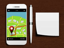 Mobile phone with gps application, pen and clean note lying on d Royalty Free Stock Photo