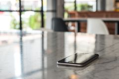 Mobile phone on granite table in blurred cafe Royalty Free Stock Images