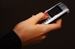 Mobile phone with hand. Woman sending a SMS message with her mobile phone Royalty Free Stock Images