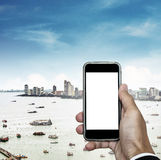 Mobile phone on hand with cityscape view and blue sky, and copy space on phone screen Stock Images