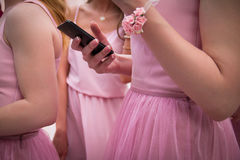 Mobile phone in hand. Girl in pink dress holds a mobile phone in her hand Royalty Free Stock Image