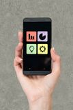Mobile phone in hand. On gray background Royalty Free Stock Photo