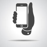 Mobile phone in hand icon on a grey background Stock Image