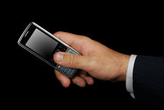 Mobile phone in hand isolated with path. Mobile phone in hand isolated on black background with clipping path Stock Image