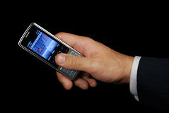 Mobile phone in hand isolated with path. Mobile phone in hand isolated on black background with clipping path Stock Photography