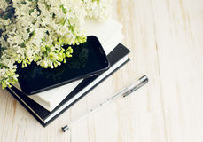 Mobile phone, handle and a bouquet of a white lilac on the books Stock Photography