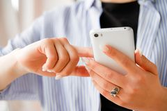 Mobile phone in the hands of a stylish fashion girl freelancer. A young woman in a black t-shirt and striped shirt, with a stock photo
