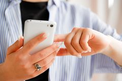 Mobile phone in the hands of a stylish fashion girl freelancer. A young woman in a black t-shirt and striped shirt, with a royalty free stock photography