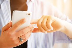Mobile phone in the hands of a stylish fashion girl freelancer. A young woman in a black t-shirt and striped shirt, with a royalty free stock photos