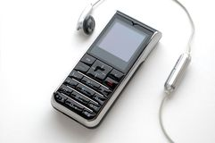 Mobile phone and the headphone. A modern mobile phone and the wired head-phone royalty free stock photo