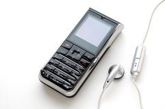Mobile phone and the headphone. A modern mobile phone and the wired head-phone stock photo