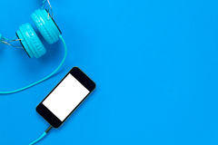 Mobile phone and headphones on blue background with cop. Top view mobile phone and headphones on blue background with copy space Royalty Free Stock Photography